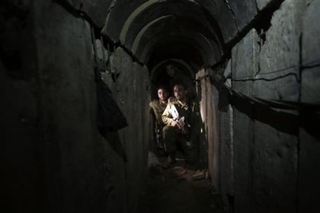 In this October13, 2013 file photo, Israeli soldiers walk through a tunnel discovered near the Israel Gaza border. Photo: AP