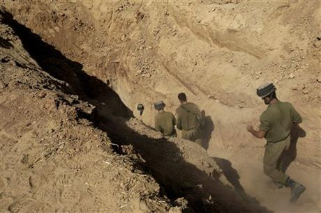 In this October 13, 2013 file photo, Israeli soldiers enter a tunnel discovered near the Israel Gaza border. Photo: AP