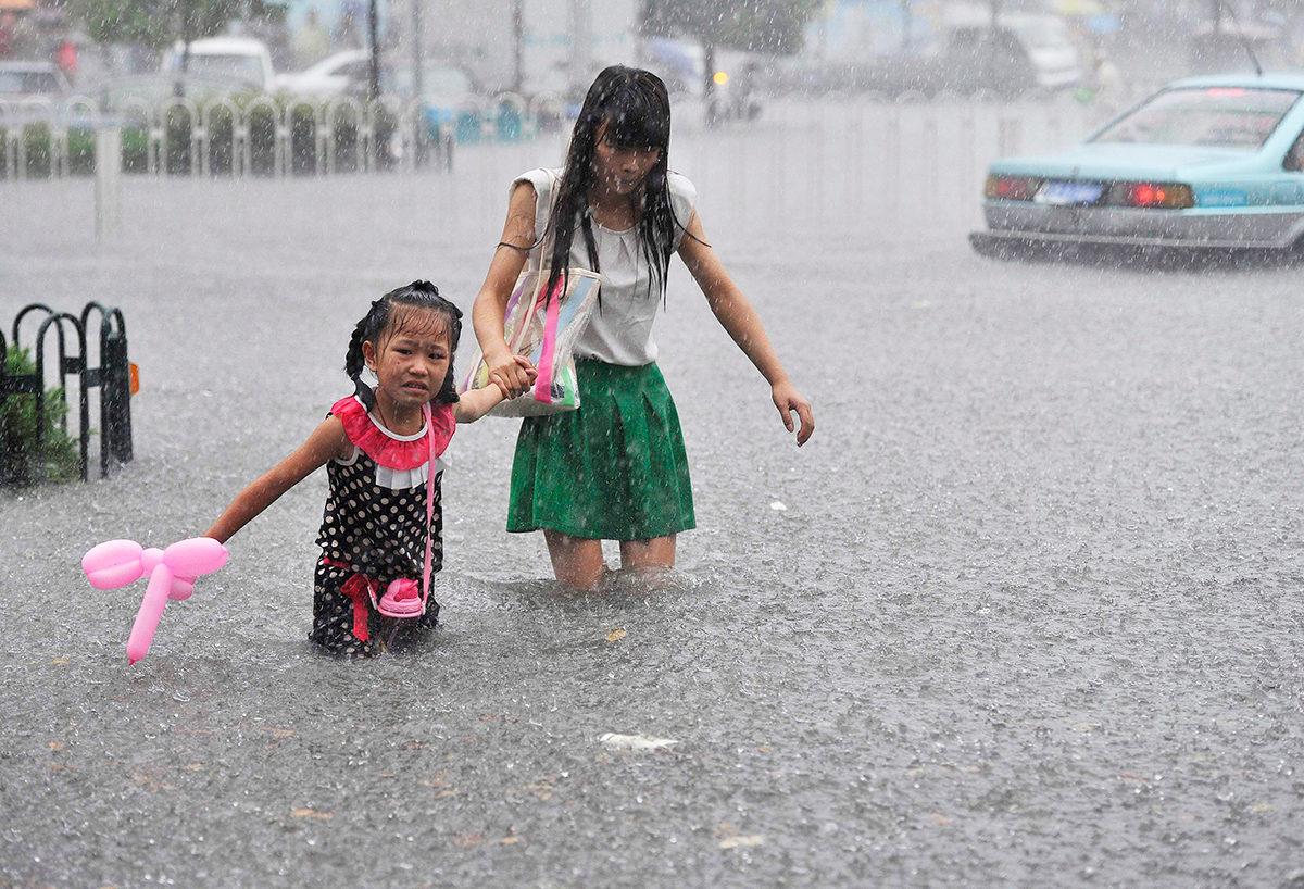 A mother holds her daughter as they wade across a flooded street during heavy rain in Hefei, Anhui province, July 27, 2014. Photo: Reuters