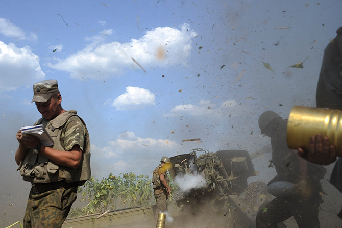 Ukrainian servicemen, who are members of an artillery section, gather near a cannon being fired during a military operation against pro-Russian separatists near Pervomaisk, Luhansk region August 2, 2014. Reuters