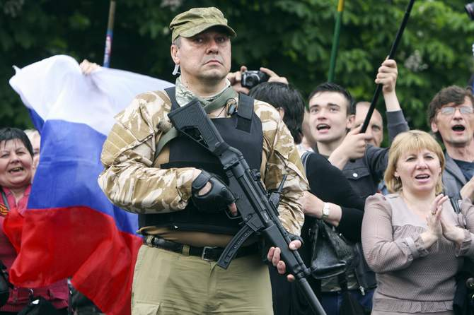 A bodyguard holds his weapon during a rally to mark and celebrate the announcement of the results of the referendum on the status of Luhansk region in Luhansk May 12, 2014. Photo: Reuters
