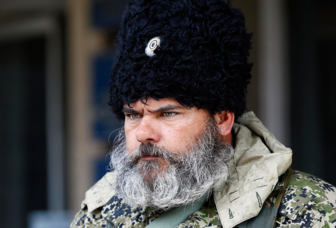 A pro-Russian armed man looks on near the mayor's office in Slaviansk on Monday. Towns in eastern Ukraine braced for military action from government forces as a deadline passed for pro-Russian separatists to disarm and end their occupation of state buildings or face a major