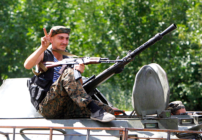 A Ukrainian serviceman gestures while driving past onboard a military armoured vehicle in the eastern Ukrainian town of Kramatorsk, August 5, 2014. Photo: Reuters