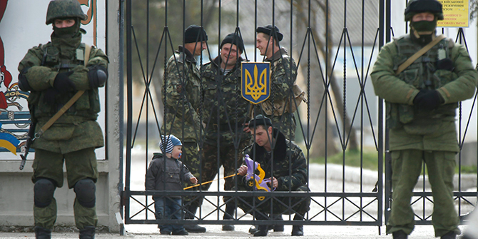 A Ukrainian serviceman plays with a child as men believed to be Russian servicemen stand in front of the gates of a Ukrainian military unit in the village of Perevalnoye outside Simferopol on March 4. Photo: Reuters