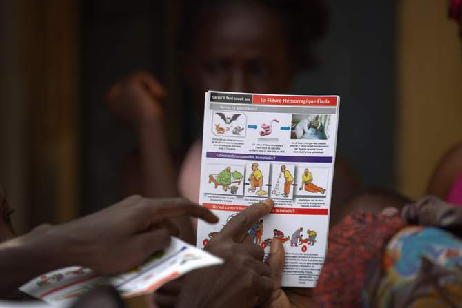 A Unicef worker shares information on Ebola and best practices to help prevent its spread with residents of the Matam neighborhood of Conakry, Guinea in this handout photo courtesy of Unicef taken August 20, 2014. The photo taken from Reuters.