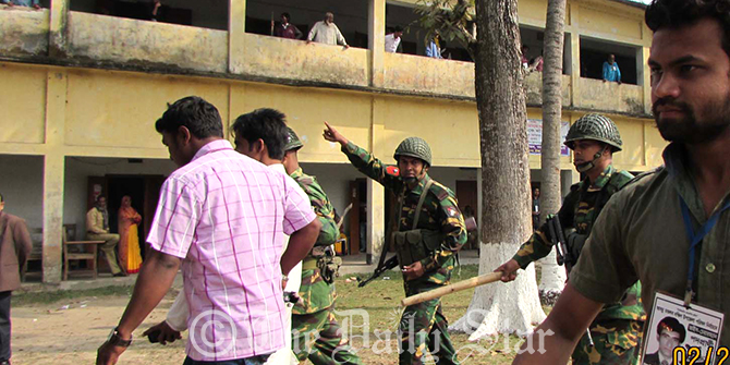 Army men throw out supporters of Awami League-backed chairman candidate, Mostofa Talukdar, from Motlob Degree College Polling Centre in Motlob South upazila of Chandpur Thursday morning. The supporters forcefully occupied the centre during upazila elections. Photo: Star