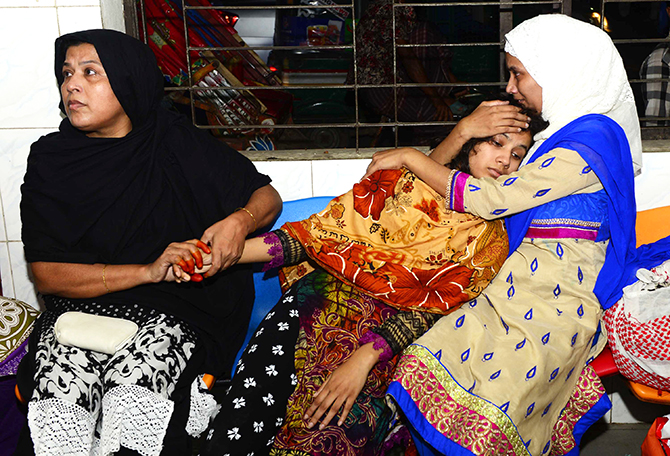 Relatives try to console Ratri, wife of deceased Simon, at Dhaka Medical College Hospital Thursday night. Simon and his father were shot near their Khilgaon home apparently by muggers. Photo: Courtesy