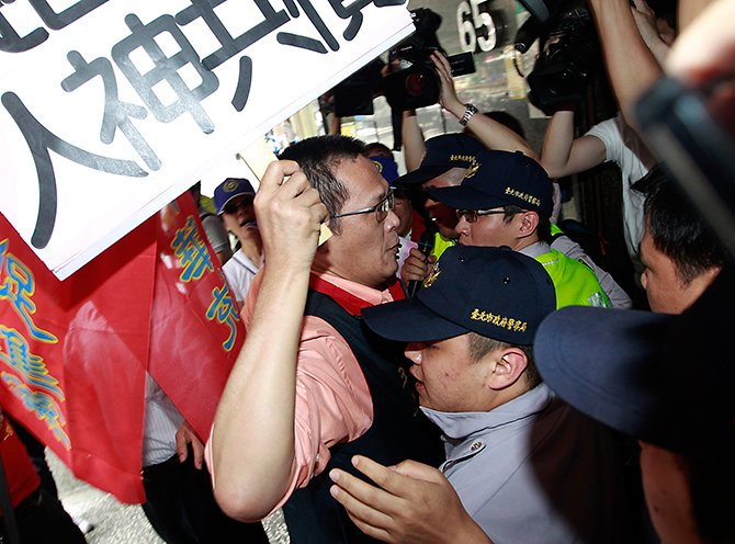 Activists holding placards scuffle with police officers during a protest in front of Vietnam Economic and Cultural office due to the anti-China protest in Vietnam, in Taipei on Thursday. The placard reads,