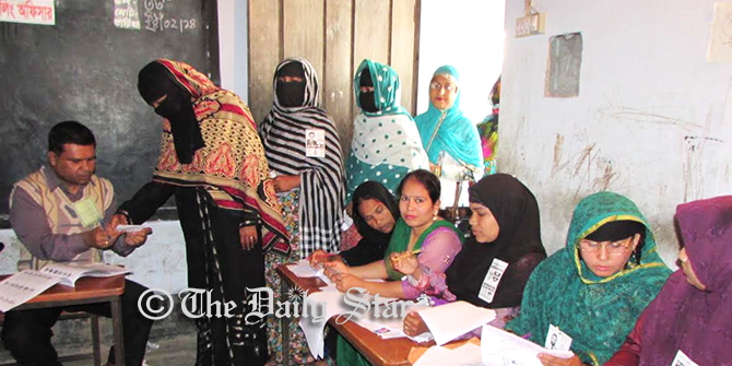 A woman is seen taking ballot to cast her vote while others waiting in a queue in Sabdarkhan Govt Primary School Polling Centre of Chandpur Sadar upazila amid festive mode on the second phase of upazila elections today. Photo: Star