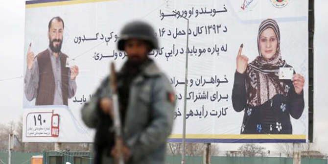 A policeman stands near a billboard for the presidential election at a checkpoint in Kabul, April 4, 2014, before Saturday's presidential election. Photo: Reuters