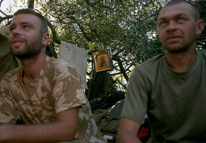 Ukrainian servicemen sit at their positions in front of a small painting near the eastern Ukrainian town of Luhansk August 26, 2014. Ukrainian President Petro Poroshenko said on Tuesday that the only effective instrument for ending bloodshed in eastern Ukraine was effective border controls with Russia, and halting arms supplies to the rebels and releasing prisoners of war. Photo: Reuters