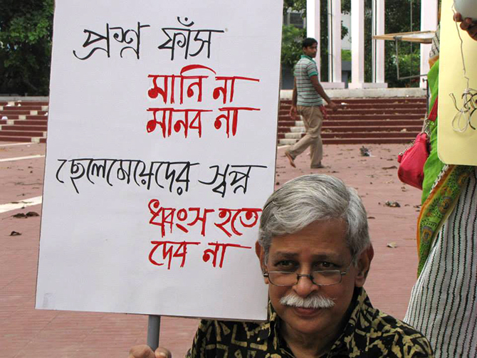 Prof Zafar Iqbal holds a placard against question paper leak in the public examinations at the Central Shaheed Minar in the capital on Friday. Photo: Courtesy